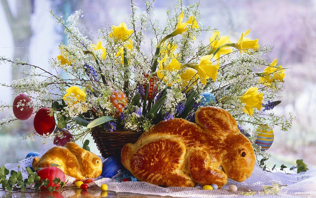 Two Easter bunnies made from dough in front of Easter flower arrangement