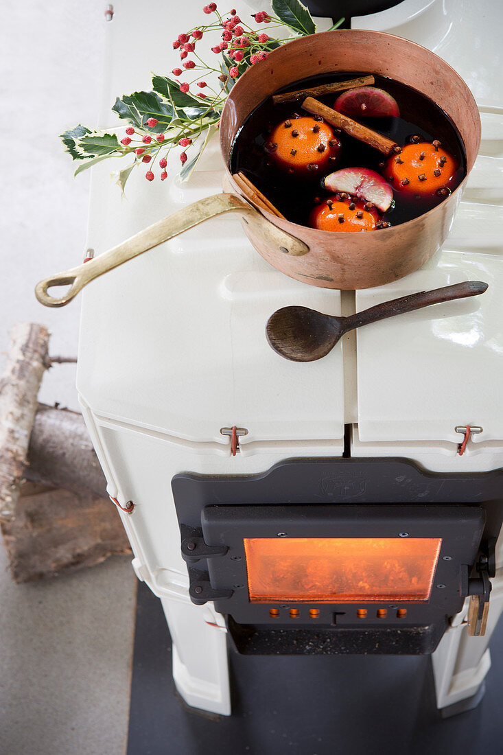 Homemade mulled wine in a copper pot on the wood stove