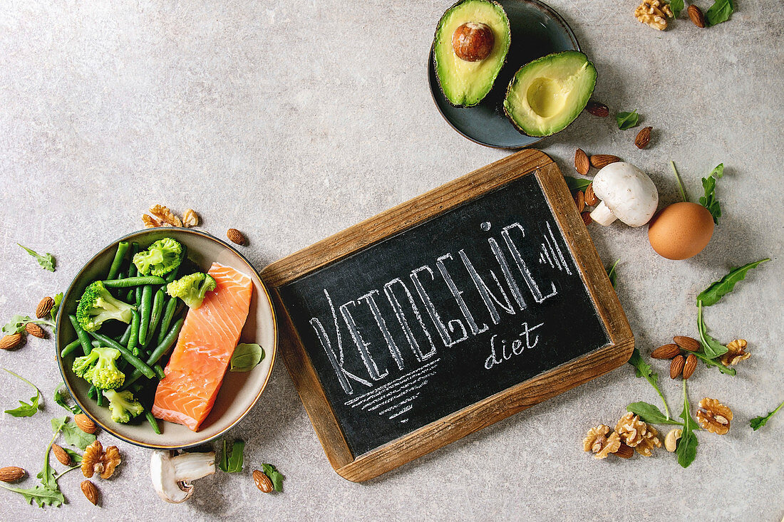 Ketogenic diet ingredients for cooking dinner. Raw salmon, avocado, broccoli, bean, olives, nuts, mushrooms, eggs in ceramic bowls