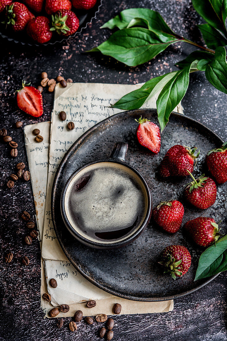 A cup of coffee on a serving plate with strawberries