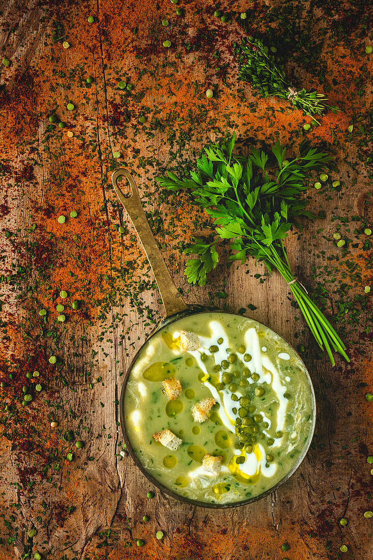 From above mashed vegetable creamy soup with small crackers, parsley and green peas on pan on wooden background