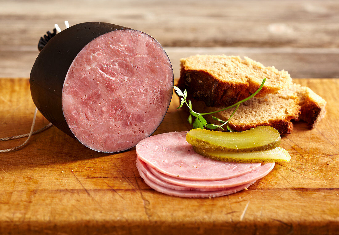 Tyrolean ham, sliced with gherkin and bread on a wooden surface