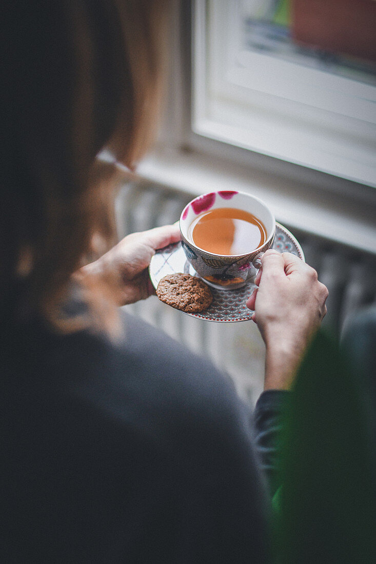 A woman with a hot tea and spiced biscuits