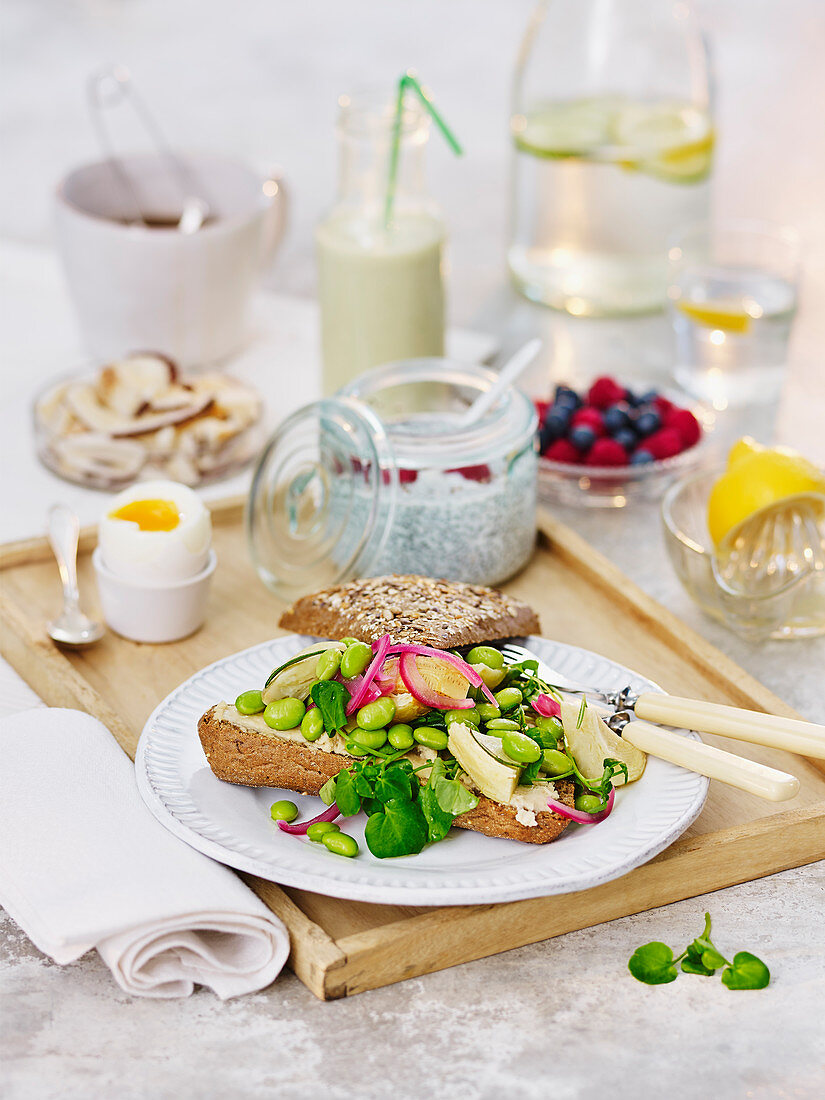 Edamame sandwich, chia pudding and a boiled egg on a wooden tray