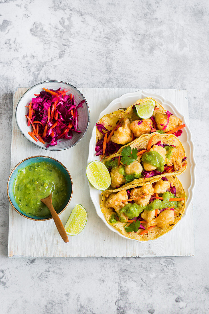 Deep fried cauliflower vegan tacos served with red cabbage salad and guacamole sauce