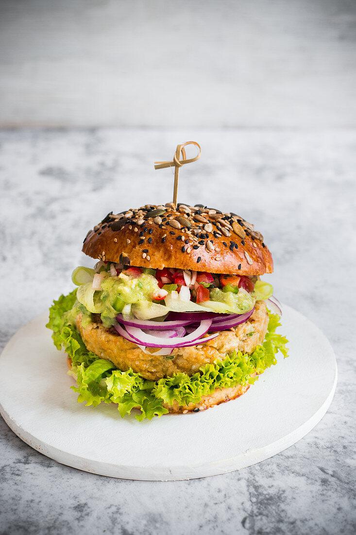 Mexican vegan burger with chickpeas pattie, guacamole and pico de gallo sauce
