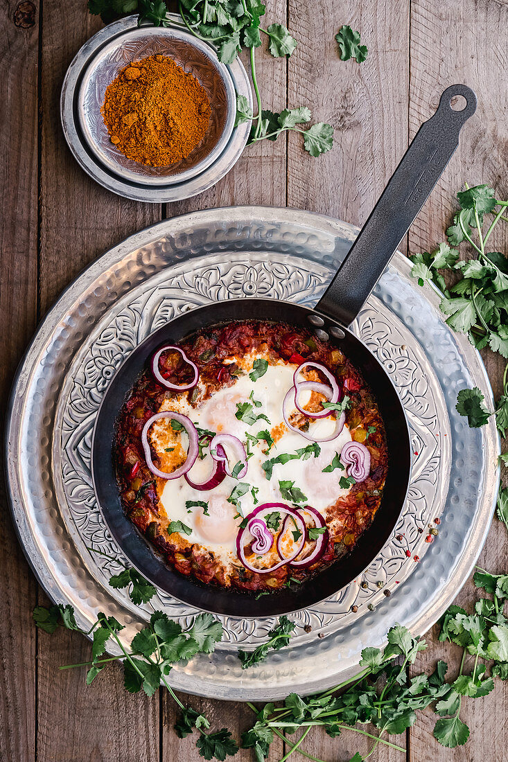 From above tasty aromatic shakshuka decorated with onion and greens on pan on silver plate and turmeric in bowl on wooden table
