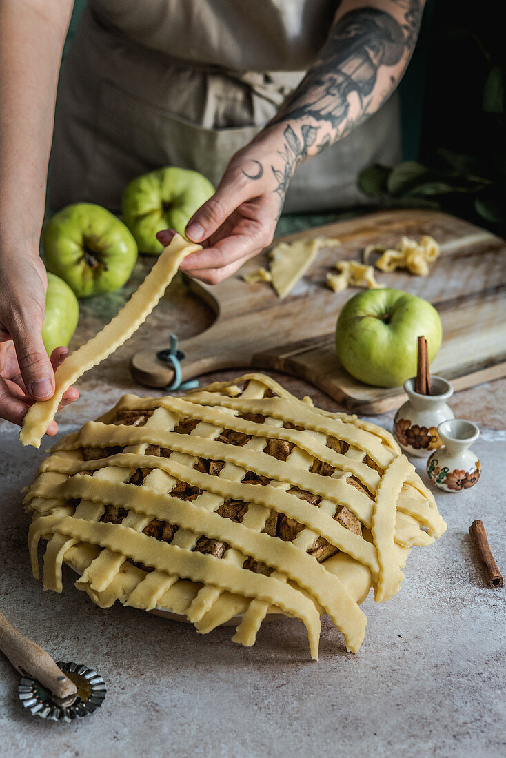 Preparing apple pie, decorating the mold with cake stripes