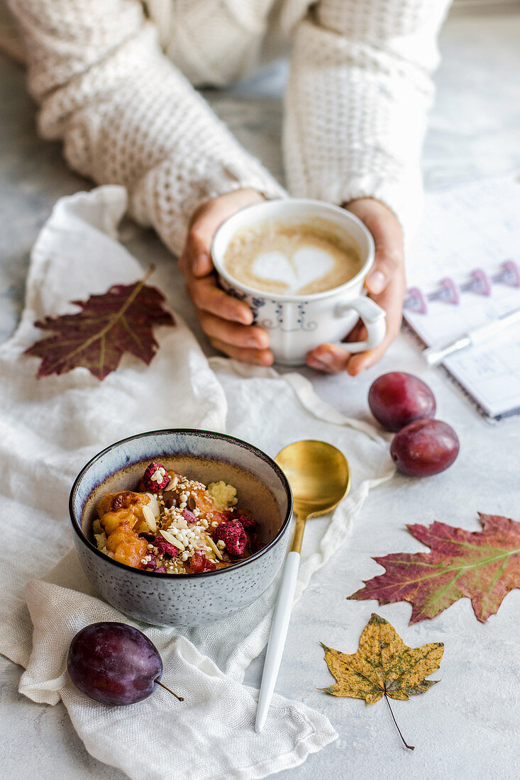 Autumn time, warming up millet with fruit, coffee in the hands of a person dressed in a warm sweater