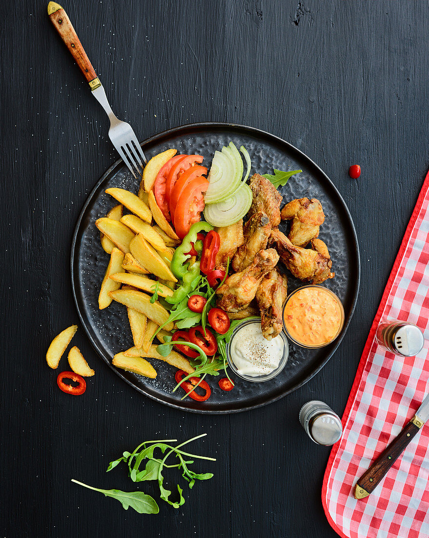 Grilled chicken drumsticks with vegetables and pommes frites