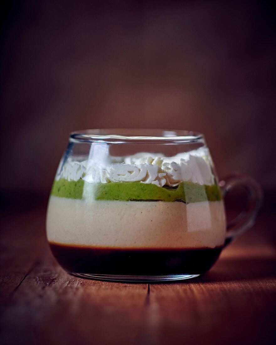 A layered dessert with coffee, coconut and avocado in a glass