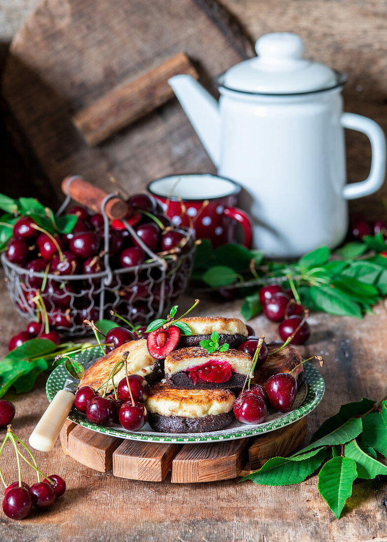 Chocolate and vanilla pancakes with cherry filling made from cottage cheese (syrniki)