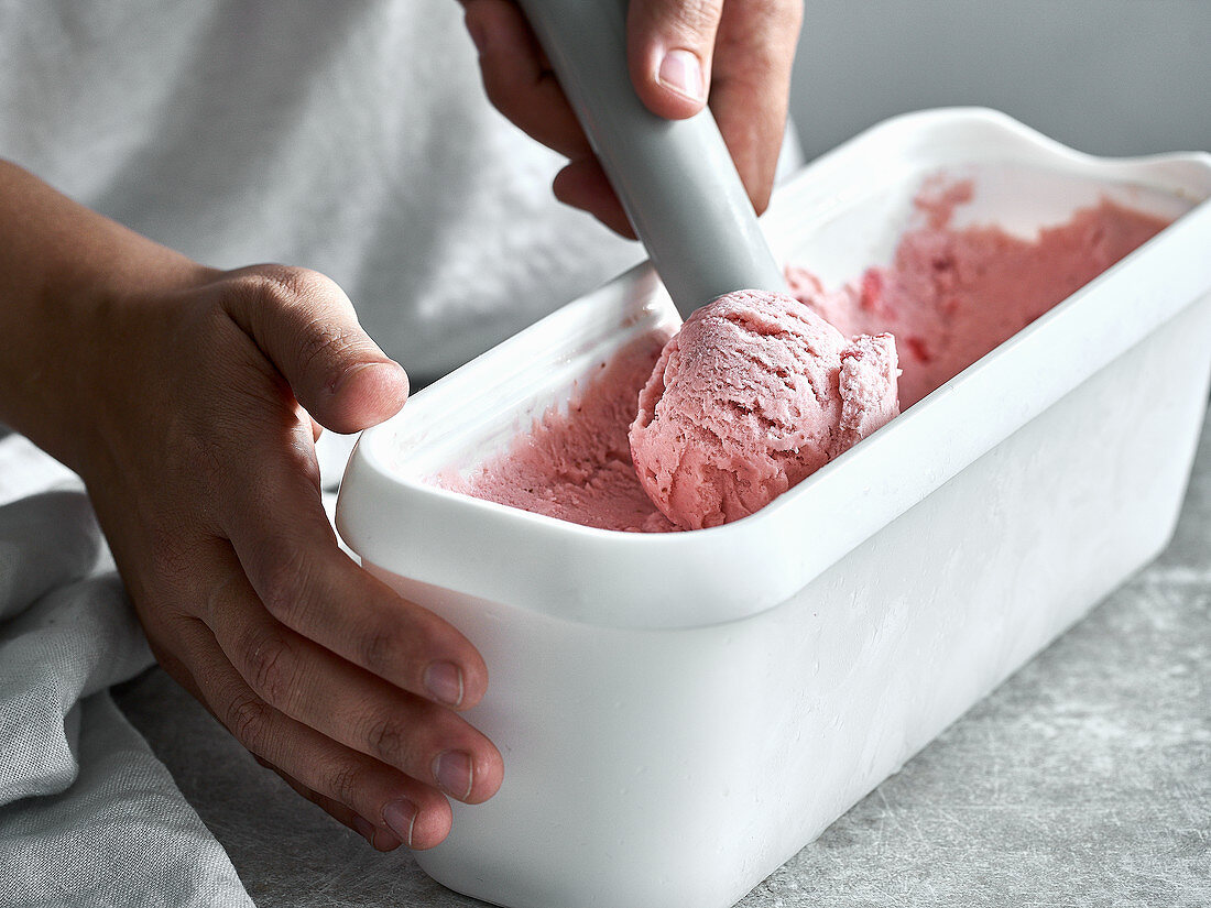 Strawberry ice cream in a container with an ice cream scoop