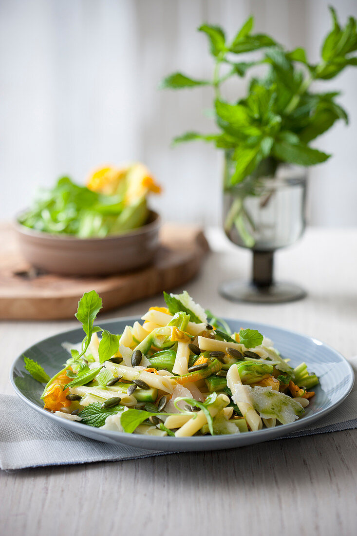Pennette with zucchini flowers, zucchini, pumpkin seeds and herbal oil