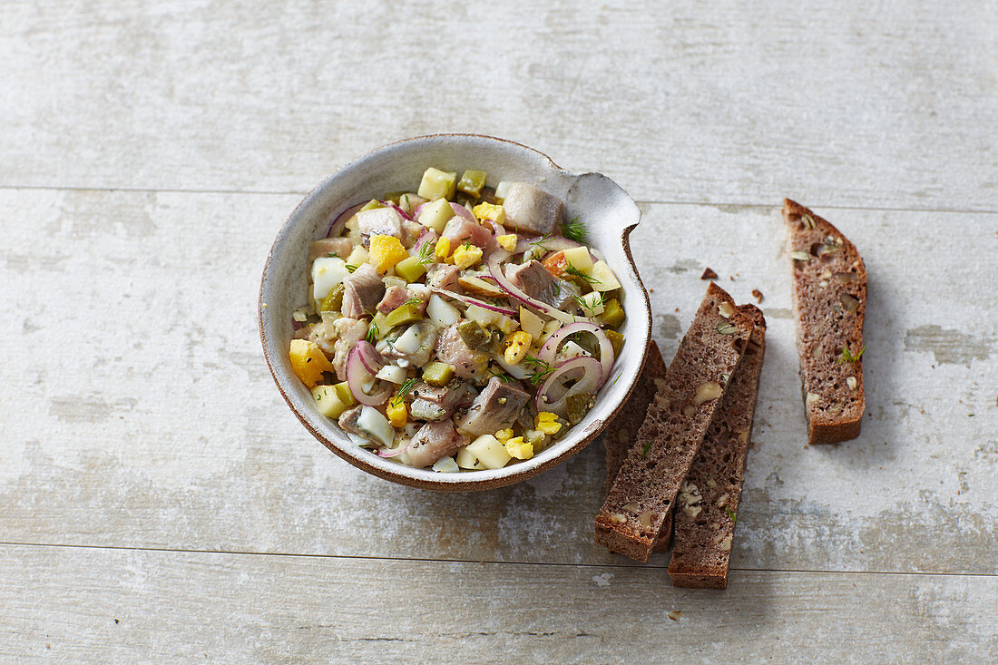Soused herring salad with hard-boiled egg, apples, onions and gherkins