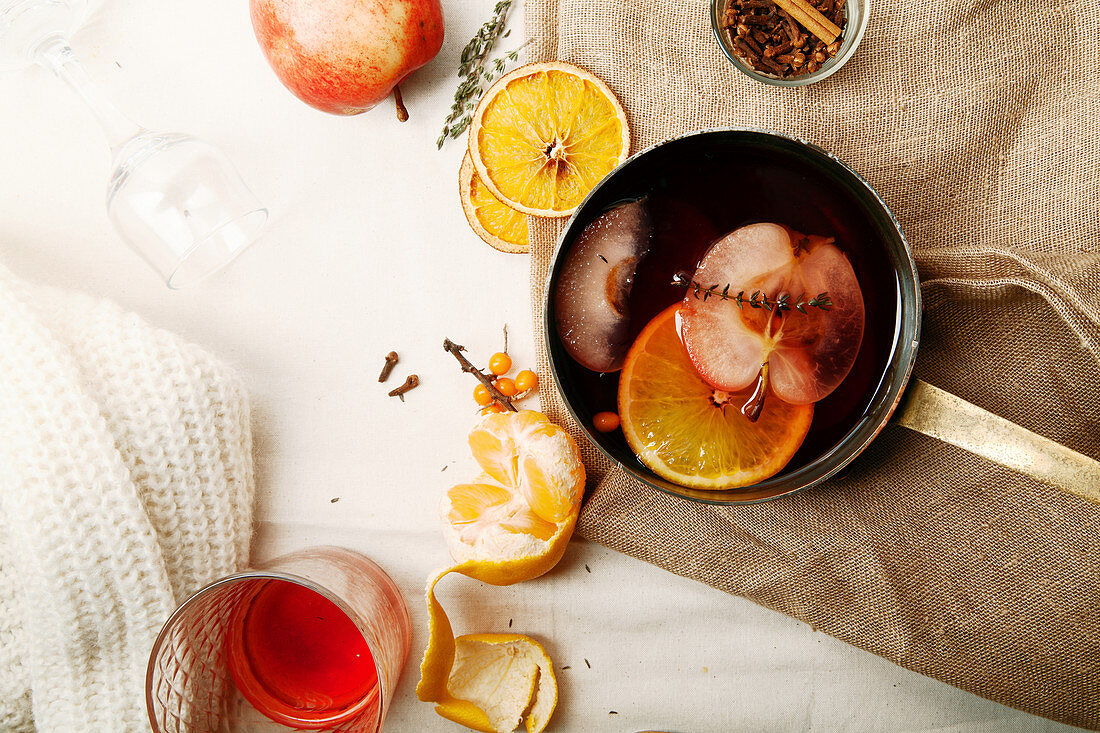 Scandinavian mulled wine in copper saucepan cooked with slices of orange, apple and thyme