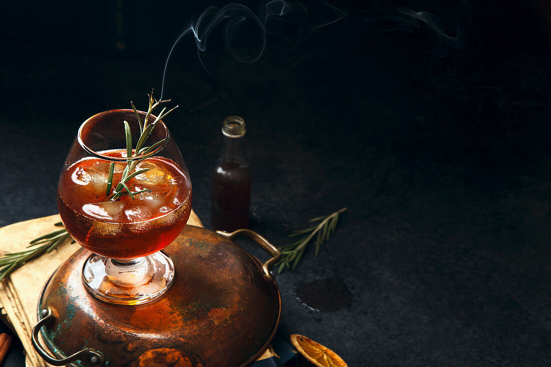 Whiskey cocktail with ice and burnt rosemary