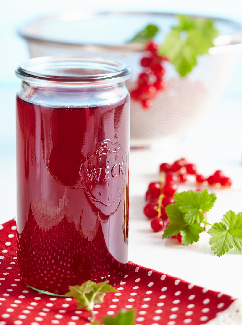 Homemade redcurrant vinegar with fresh berries and vanilla