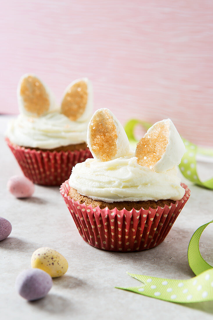 Two Easter bunny cupcakes with marshmallow ears in a pastel setting with mini eggs in the foreground