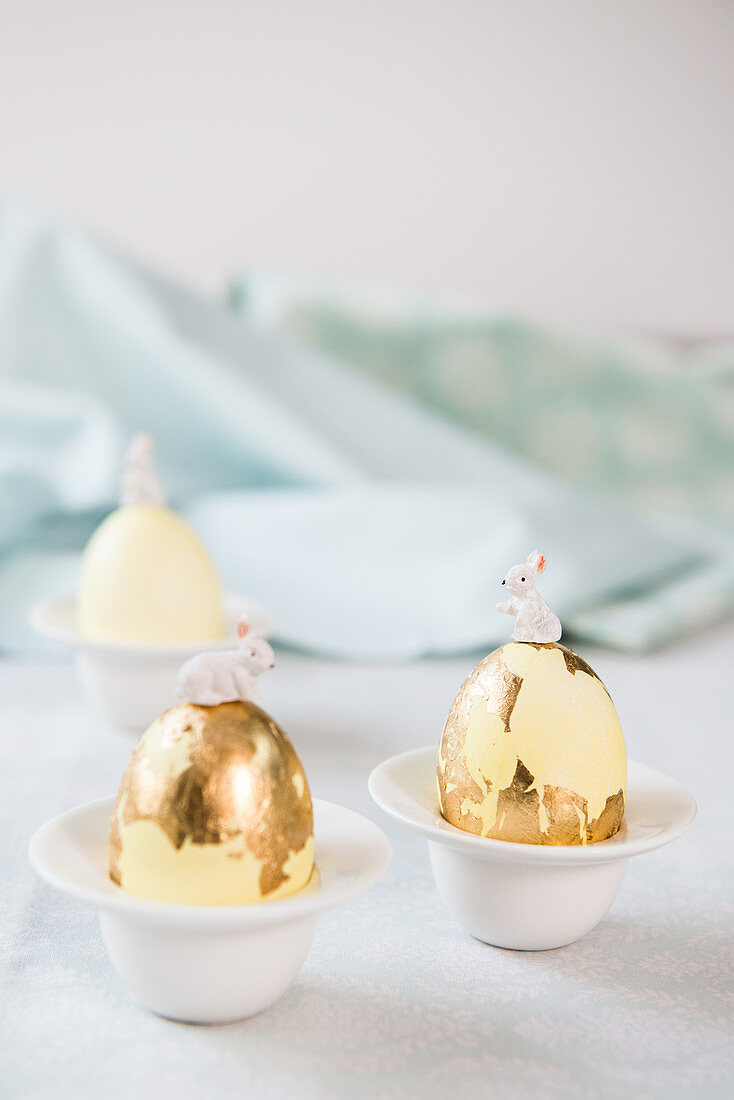 Bunnies on top of Easter eggs covered in gold leaf
