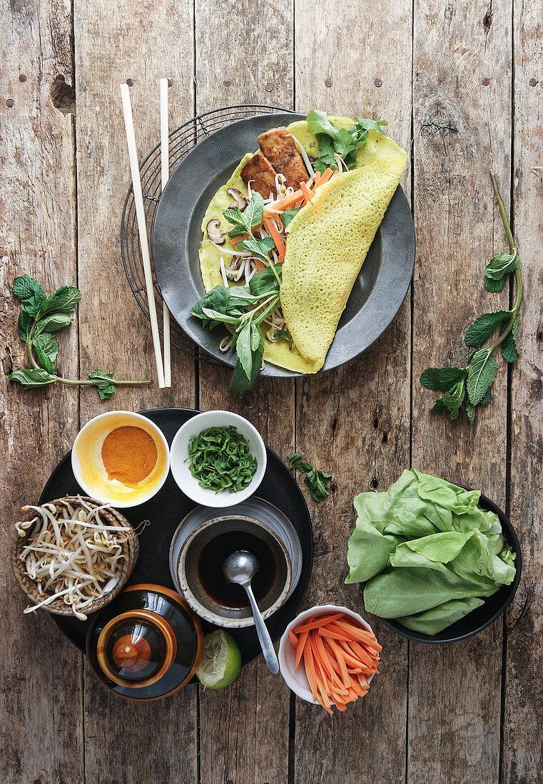 Banh Xeo (vietnamesische Reismehl-Pfannkuchen) mit verschiedenen Zutaten zum Füllen