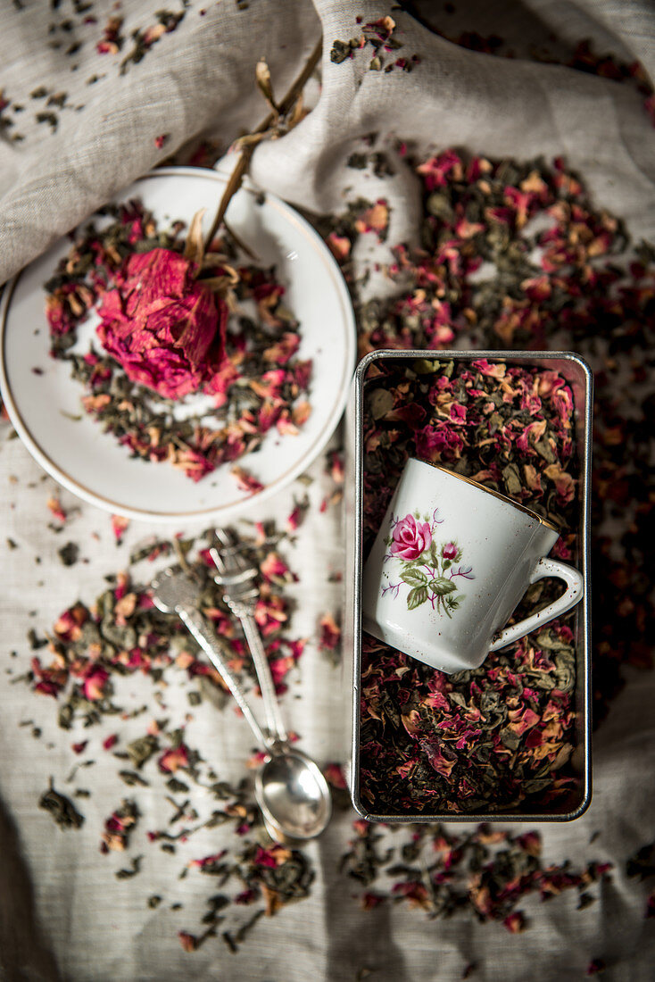 Cups with floral motif and dried rose petals in tin