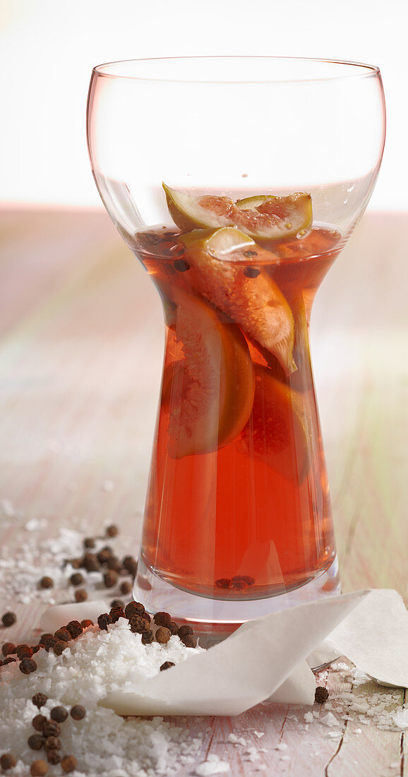 Homemade fig vinegar in a glass with pepper and sea salt