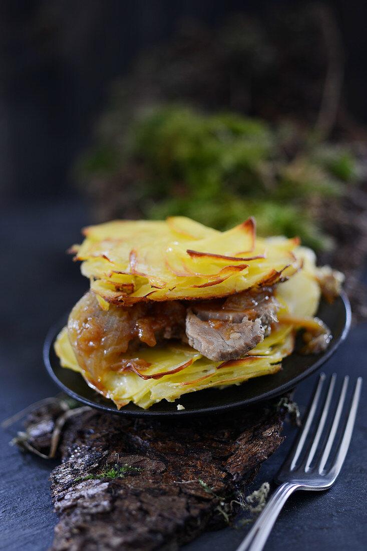 Spit-roasted pork with potato gratin