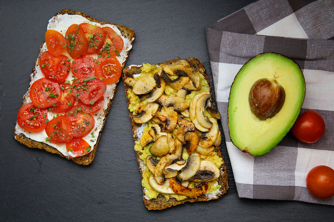 Two slices of bread, one topped with tomatoes and one topped with mushrooms