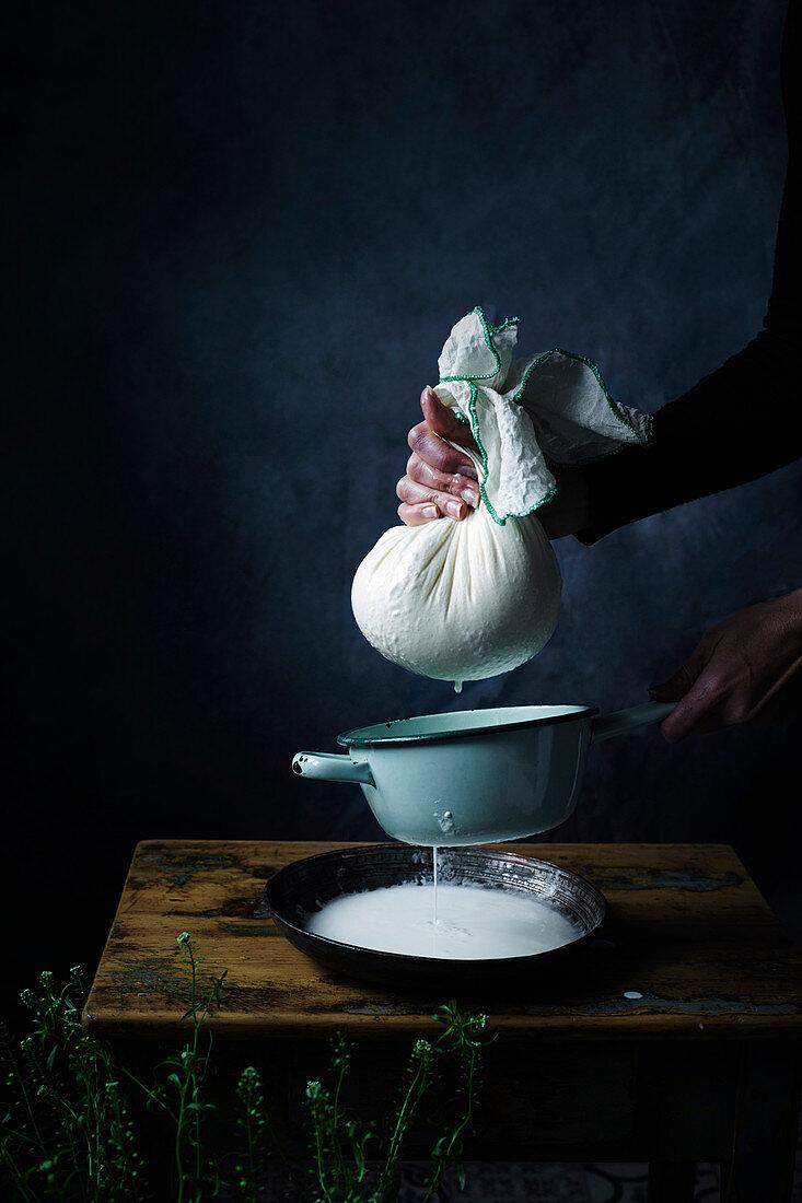 Hüttenkäse selbermachen: Käsemasse durch Mulltuch abseihen