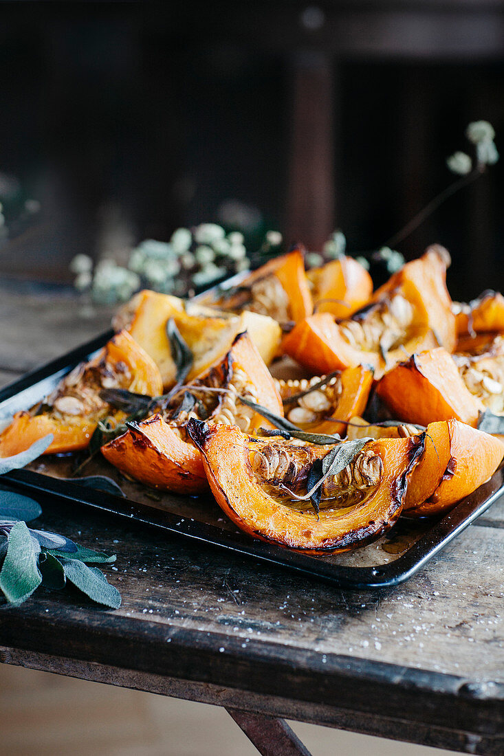 Oven roasted pumpkin slices with sage on a stove sheet