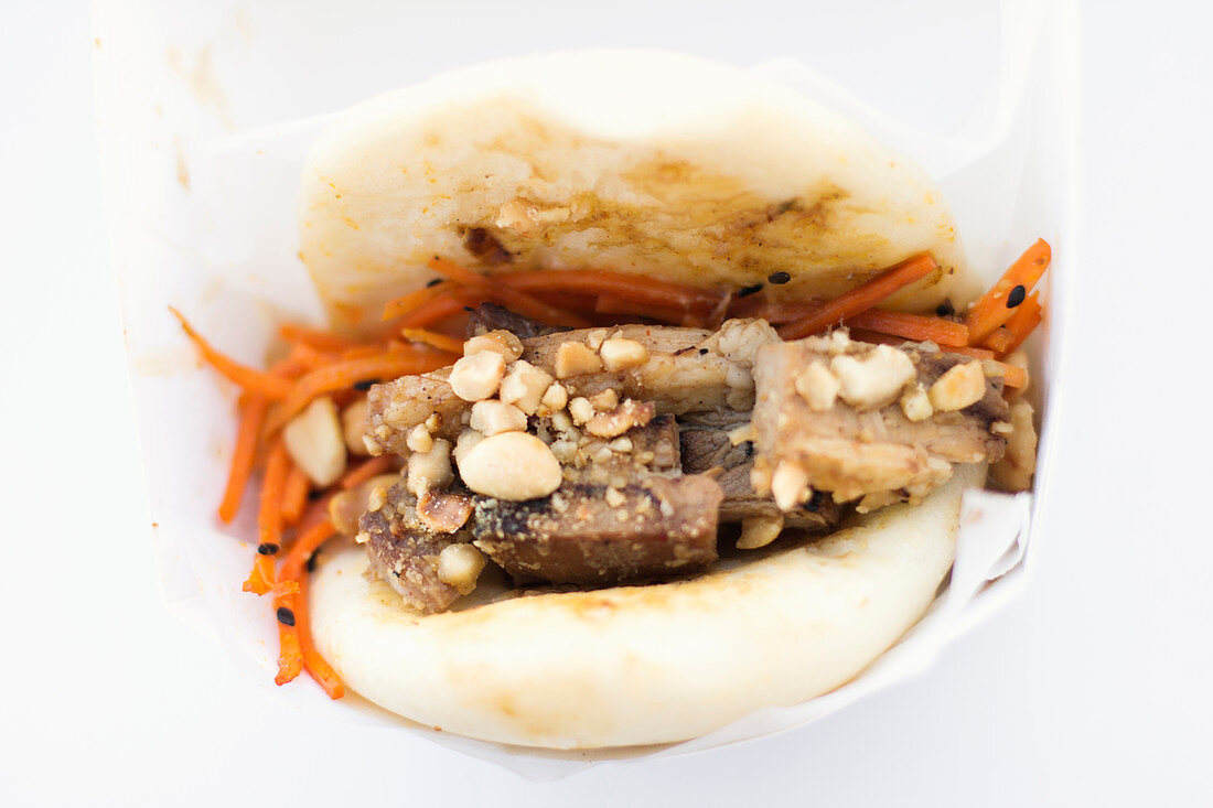 Steamed bun filled with char siu style pork belly, marinated carrots and toasted peanuts
