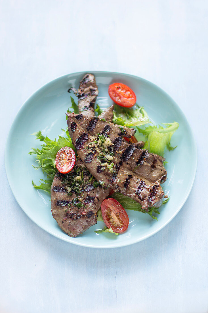 Chargrilled lamb liver slices on salad greens and grilled plum tomatoes