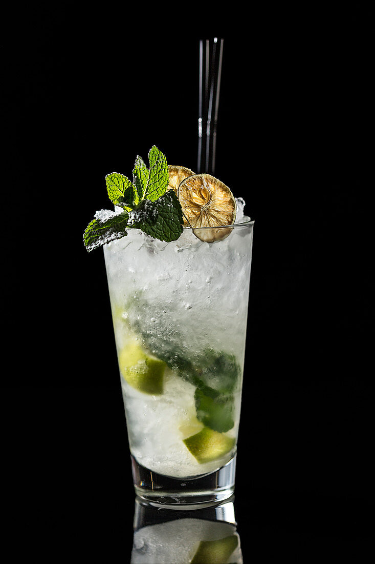 High glass with traditional Mojito cocktail garnished with dried lime and mint on black background