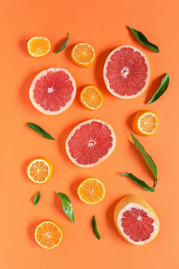 Tangerine and grapefruit slices on orange background