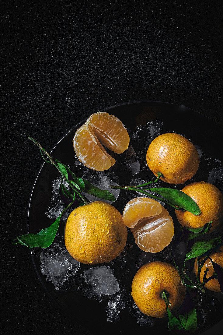 Mandarinen mit Eiswürfeln auf schwarzem Untergrund