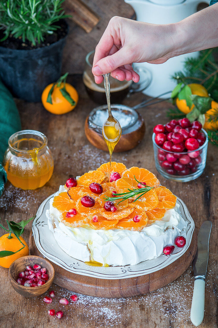 Mandarinen-Pavlova zubereiten, Honig auf Mandarinenscheiben träufeln