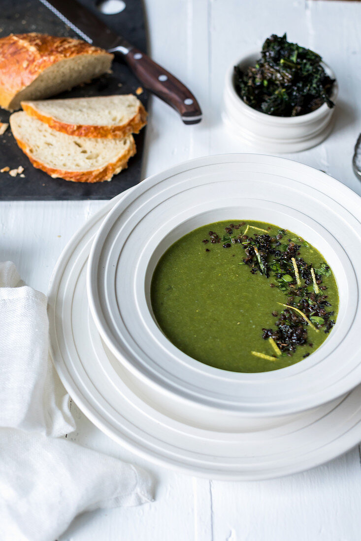 Spinach soup garnished with sauteed lentils, kale crisps, pasley and lemon zest