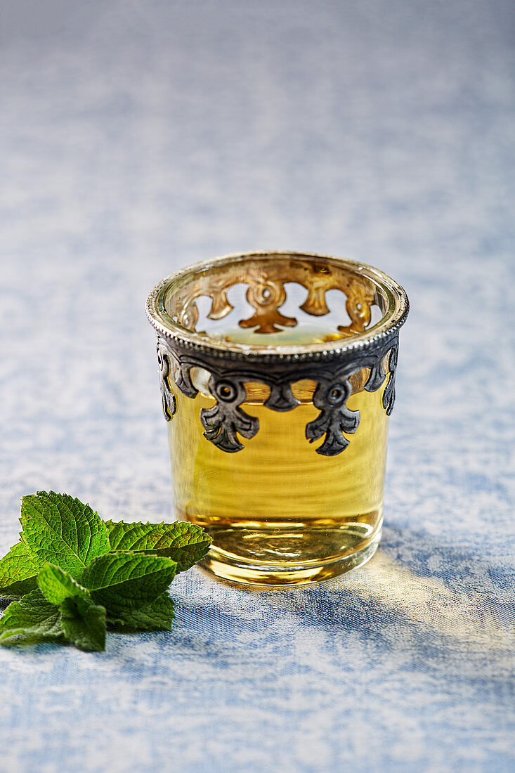 Mint tea in a oriental glass with fresh mint leaves