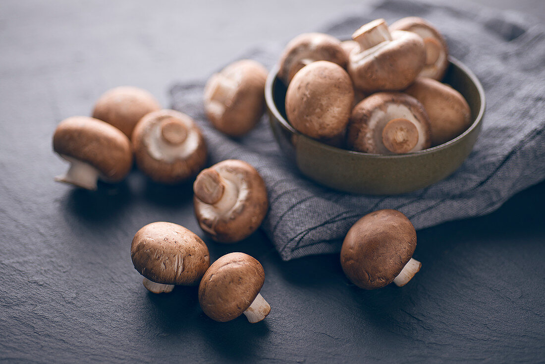 Fresh brown mushrooms in a bowl and on a slate background