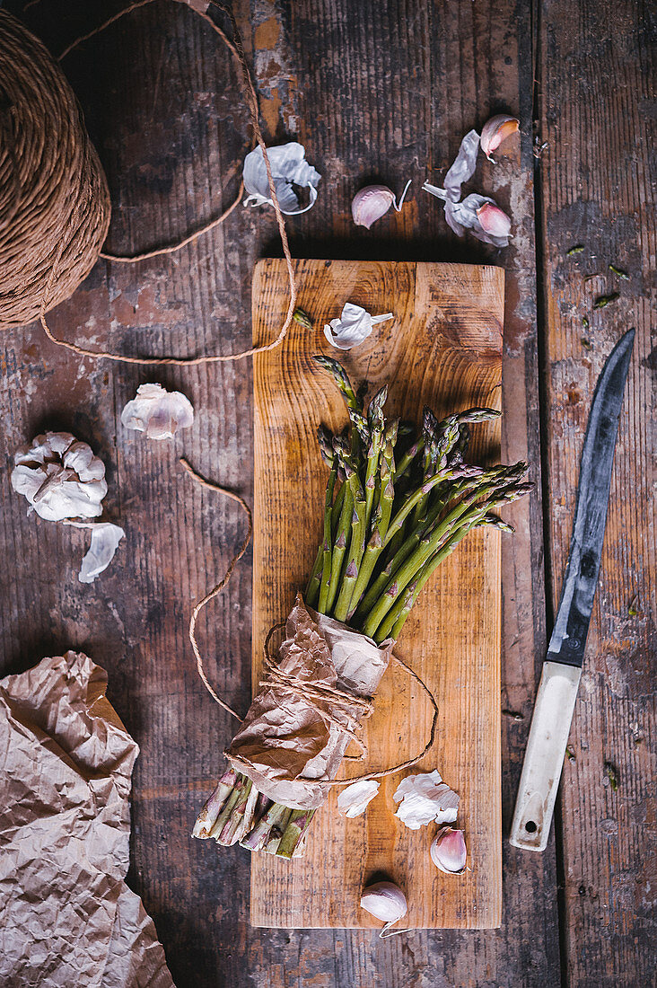 A bunch of green asparagus, garlic bulbs, and a knife on a wooden table