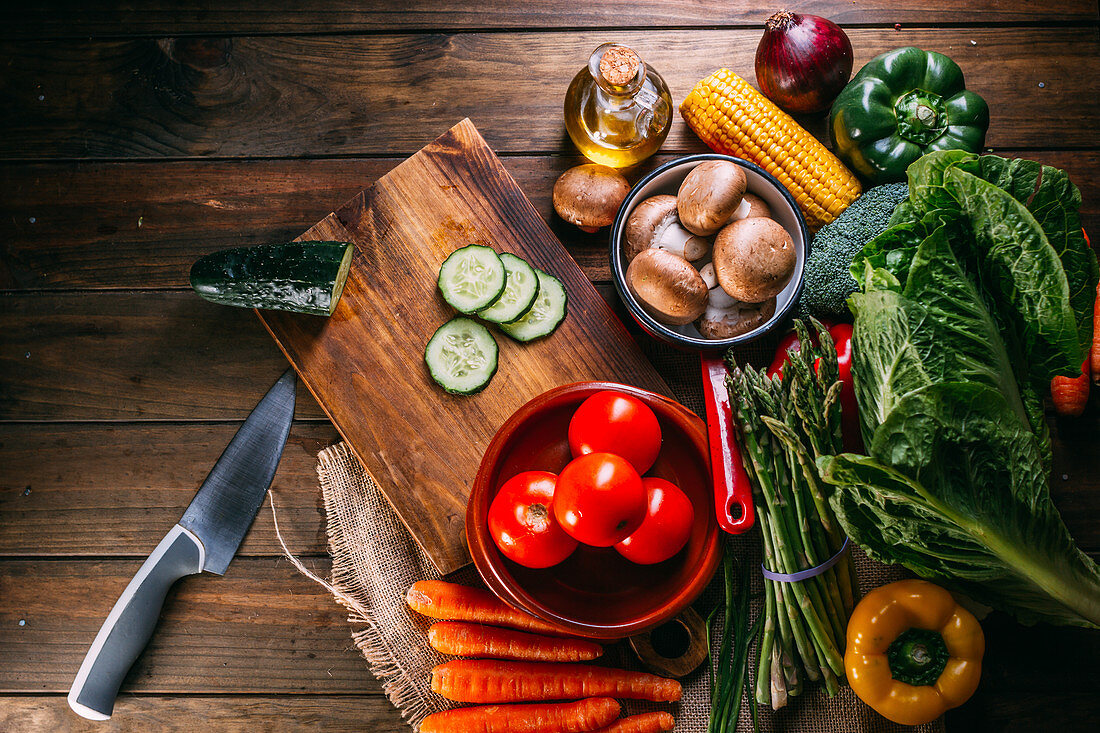 From above assorted fresh vegetables lying on lumber table near sharp knife and cutting board