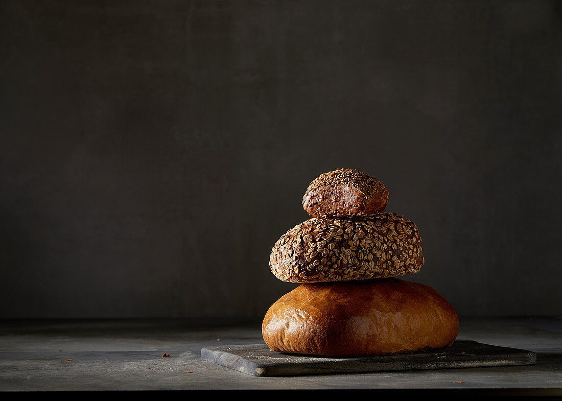Two breads and a bread roll, stacked against a dark background
