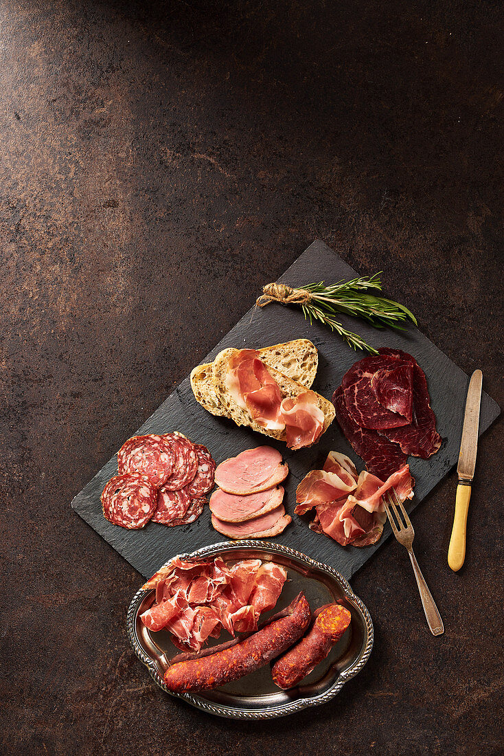 Selection of cured meats with bread and rosemary