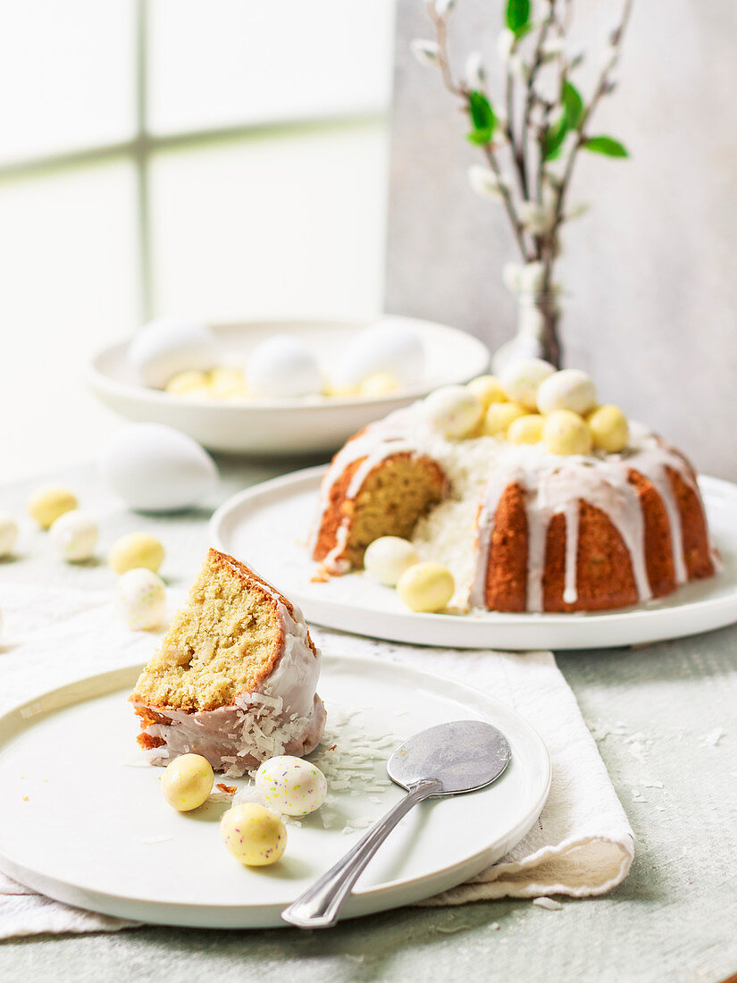 Coconut Easter cake with white chocolate eggs, sliced