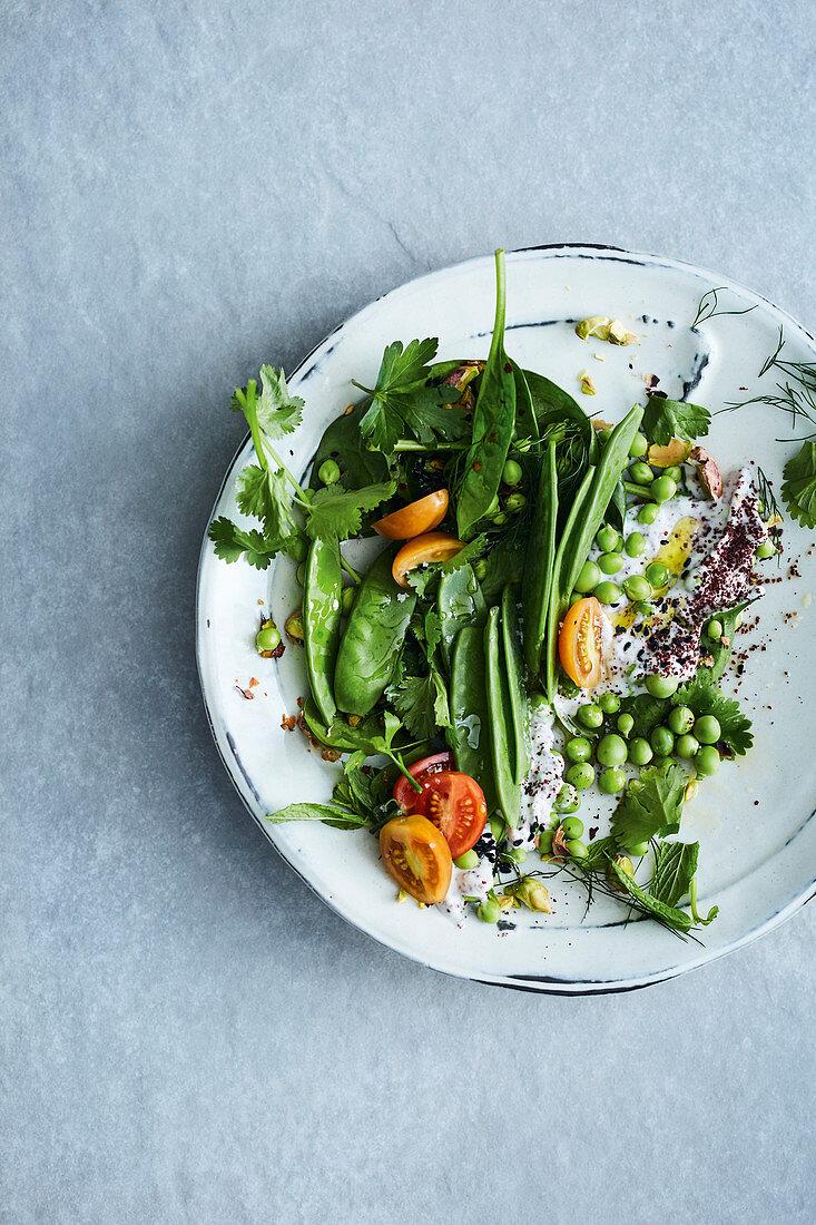 Mange tout with peas, yoghurt sauce and black caraway seeds