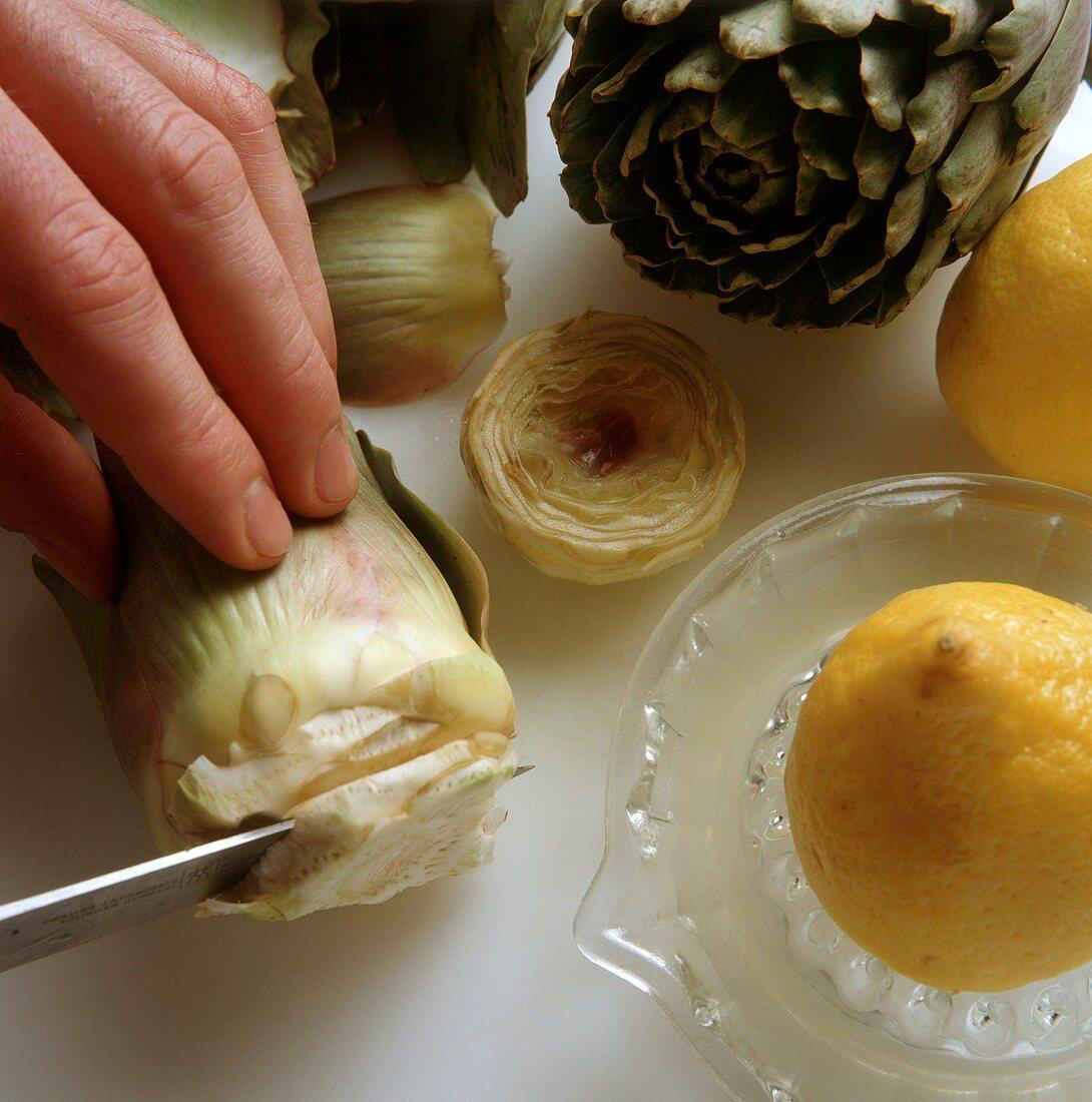 Cutting artichokes & rubbing cut surfaces with lemon juice