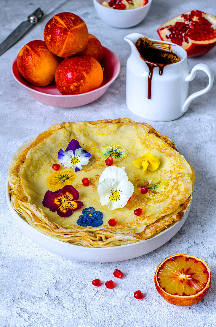 Thin pancakes with violets, chocolate sauce, red oranges and pomegranate