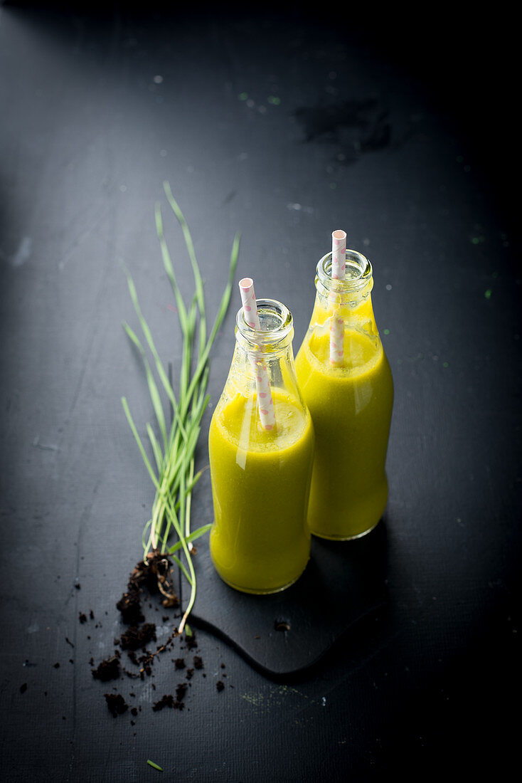 Mango and wheatgrass smoothies in glass bottles