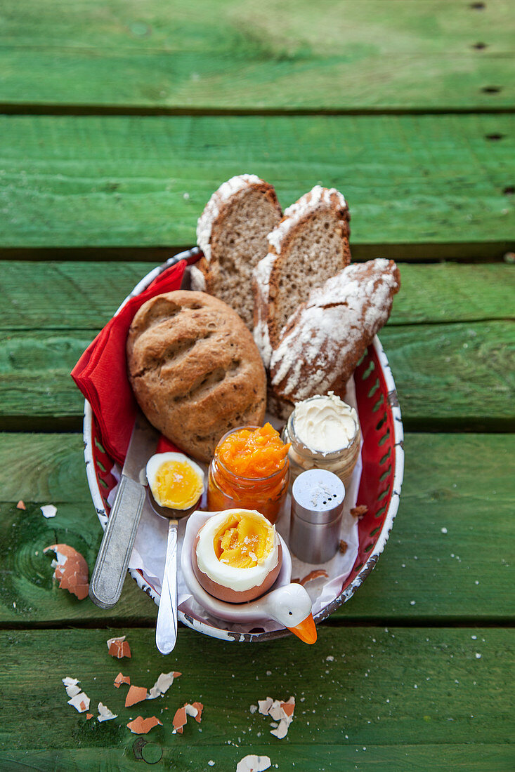 A breakfast basket with a boiled egg, wholemeal bread and orange and carrot marmalade